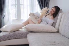 La giovane donna asiatica che odora la coda asciutta del coniglio fiorisce sul letto nel liv Immagine Stock Libera da Diritti