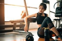 La giovane donna asiatica che si rilassano nella palestra di forma fisica ed il club di sport concentrano Fotografie Stock Libere da Diritti