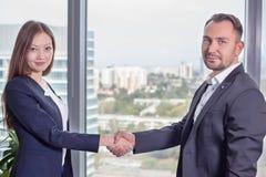 La giovane donna asiatica di affari in vestito stringe le mani con il suo socio commerciale Fotografie Stock