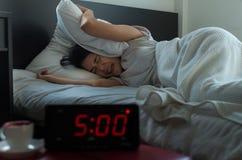 La giovane donna asiatica odia ottenere sollecitata svegliando presto l'orologio del ` di 5 o, sveglia immagine stock libera da diritti