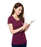 La giovane donna asiatica prende nota sulla lavagna per appunti Fotografia Stock