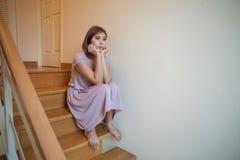 La giovane donna asiatica si siede da solo sulle scale Immagine Stock