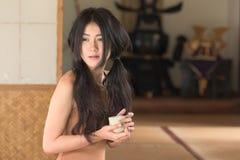 La giovane donna asiatica si siede nella stanza di stile del Giappone fotografia stock libera da diritti