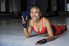 La giovane donna asiatica sudata felice e bella nello sport copre l'allungamento sul concetto sportivo hy di stile di vita del do Immagini Stock Libere da Diritti