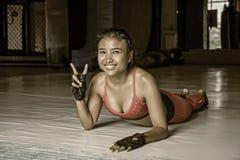 La giovane donna asiatica sudata felice e bella nello sport copre l'allungamento sul concetto sportivo hy di stile di vita del do Fotografie Stock Libere da Diritti