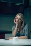 La giovane donna aspetta dal telefono su una cucina di notte Immagini Stock