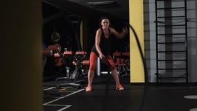 La giovane donna atletica che fa un certo crossfit si esercita con una corda archivi video