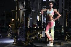 La giovane donna atletica che posa e che fa l'allenamento di forma fisica con pesa Fotografia Stock Libera da Diritti