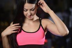 La giovane donna atletica che posa e che fa l'allenamento di forma fisica con pesa Immagini Stock