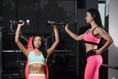 La giovane donna atletica che posa e che fa l'allenamento di forma fisica con pesa Fotografie Stock