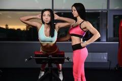 La giovane donna atletica che posa e che fa l'allenamento di forma fisica con pesa Immagine Stock Libera da Diritti
