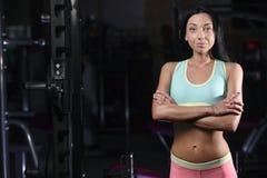 La giovane donna atletica che posa e che fa l'allenamento di forma fisica con pesa Fotografia Stock