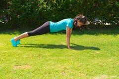 La giovane donna atletica fa l'addestramento di spinta-UPS Fotografie Stock