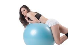 La giovane donna atletica si è esercitata con una palla blu della stabilità Fotografia Stock