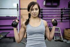 La giovane donna atletica si occupa delle teste di legno nella palestra Fotografia Stock Libera da Diritti