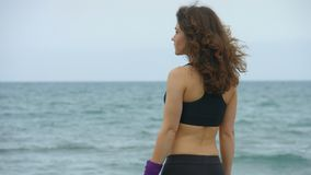 La giovane donna attiva smette di esaminare la vista sul mare stupefacente Spruzzatura salata delle onde del mare stock footage