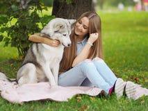 La giovane donna attraente abbraccia il cane divertente del husky siberiano Fotografie Stock