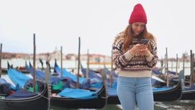 La giovane donna attraente che resta sul lungomare e esamina il suo telefono Poi lei che sorride e che ride stock footage