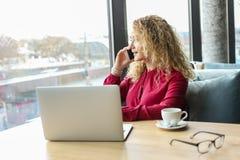 La giovane donna attraente che si siede alla caffetteria con il suo computer portatile alla moda, cappuccino bevente, parlando su Immagini Stock Libere da Diritti