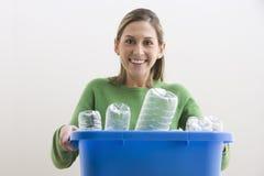 La giovane donna attraente che tiene un blu ricicla lo scomparto Immagine Stock Libera da Diritti