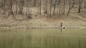 La giovane donna attraente con il cappello rosso vaga in foresta dal lago congelato archivi video