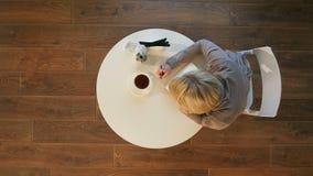 La giovane donna attraente di affari fa le note in un taccuino che si siede in caffè video d archivio
