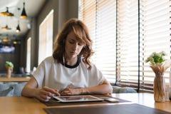 La giovane donna attraente ha concentrato la lettura del libro elettronico sulla sua compressa digitale Fotografie Stock