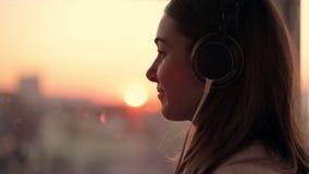 La giovane donna attraente indossa ascoltare la musica sullo smartphone a fondo vago città con il tramonto Godere video d archivio