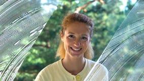 La giovane donna attraente lava una finestra che sorride alla macchina fotografica Colpo del carrello video d archivio