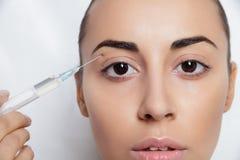 La giovane donna attraente ottiene l'iniezione cosmetica Fotografia Stock