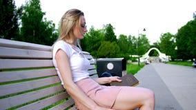 La giovane donna attraente scrive un messaggio sullo smartphone e prende un vecchio libro che si siede sul banco archivi video