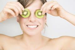 La giovane donna attraente semina il kiwi Fotografia Stock