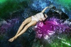 La giovane donna attraente sexy castana in vestiti bianchi gode dell'immersione subacquea nella piscina fotografia stock libera da diritti