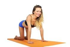 La giovane donna attraente sexy di misura alla palestra che fa l'esercizio di yoga e che allunga sulla stuoia nella meditazione e Fotografia Stock