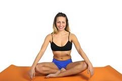 La giovane donna attraente sexy di misura alla palestra che fa l'esercizio di yoga e la posizione che si siede sulla stuoia nella Fotografia Stock
