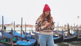 La giovane donna attraente sorridente che resta sul lungomare e esamina il suo telefono archivi video
