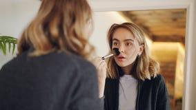 La giovane donna attraente sta guardando nello specchio e sta mettendo su trucco con la spazzola ed i cosmetici decorativi Fronte stock footage
