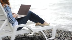 La giovane donna attraente sta lavorando al computer portatile vicino con il bello paesaggio dell'acqua e della natura sulla loca archivi video