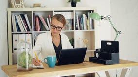 La giovane donna attraente sta lavorando nell'ufficio moderno che si siede alla tavola, facendo uso del computer portatile e scri video d archivio