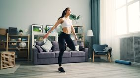 La giovane donna attraente sta occupando a casa facendo gli esercizi per perdita di peso archivi video