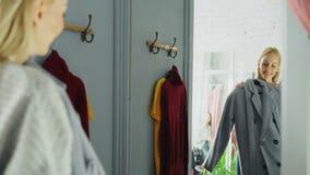 La giovane donna attraente sta provando il cappotto elegante mentre stare nella stanza adatta è boutique dell'abbigliamento Sta e stock footage