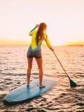 La giovane donna attraente sta sulla pagaia che pratica il surfing con i bei colori dell'alba o del tramonto Fotografia Stock