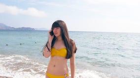 La giovane donna attraente in un costume da bagno sta parlando sul telefono cellulare su una spiaggia del mare Ragazza seria in b Fotografia Stock Libera da Diritti