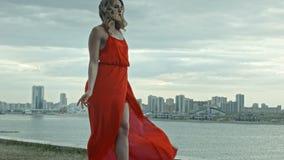 La giovane donna attraente in un vestito rosso controlla il citi stock footage