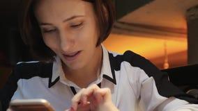 La giovane donna attraente utilizza il suo telefono cellulare in un ristorante accogliente del caff? ? sorridente e felice archivi video