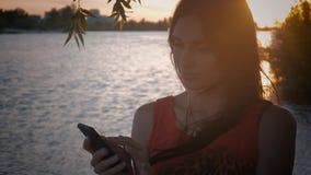 La giovane donna attraente utilizza lo smartphone al tramonto Una ragazza sveglia sorride ed utilizza un cellulare al fondo del m stock footage
