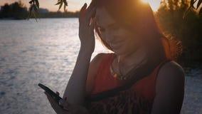 La giovane donna attraente utilizza lo smartphone al tramonto Una ragazza sveglia sorride ed utilizza un cellulare al fondo del m archivi video
