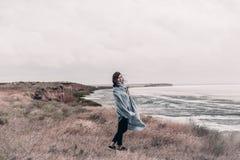 La giovane donna avvolta in coperta calda sta stando sulla costa del mare in tempo ventoso immagini stock libere da diritti