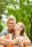 La giovane donna bacia il suo partner fotografia stock libera da diritti