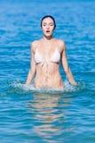 La giovane donna bagnata in bikini salta dell'acqua fotografie stock libere da diritti